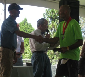 Dave collecting his belt buckle and accepting congratulations from Tim Twietmeyer, who won Western States five times among his 25 sub-24 hour finishes in the race.